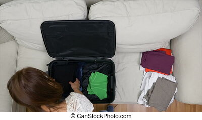 Young woman carefully preparing travel bag for summer trip