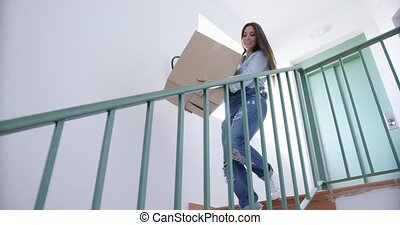 Young woman carrying a carton downstairs - Young woman...