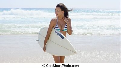 Young woman carrying a surfboard across the beach as she...
