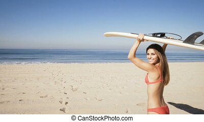young woman carrying a surfboard at the beach. - young woman...