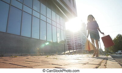 Young woman carrying shopping bags while walking along the street