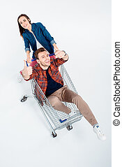 woman carrying shopping cart with happy man showing thumbs up