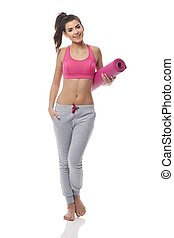 Young woman carrying yoga mat