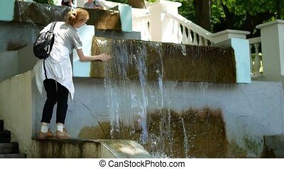Young woman catches a drop from a fountain.