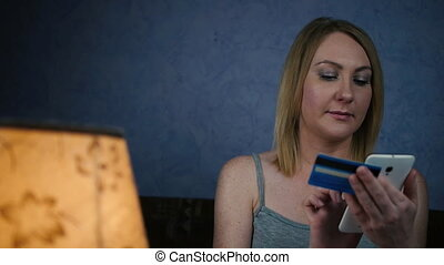 Young woman caucasian hands buying goods from the internet on smartphone with credit card
