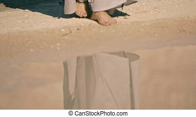 young woman cautiously enters the lake water. body part, - A...