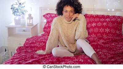 Young woman celebrating alone at Christmas sitting barefoot...