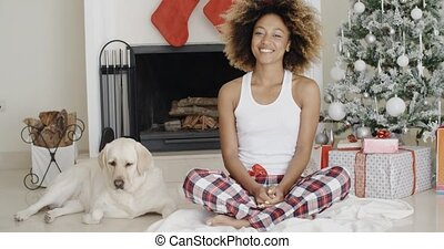 Young woman celebrating Christmas with her dog - Attractive...