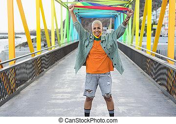 Young woman celebrating gay pride holding rainbow flag symbol of Lgbtq social movement