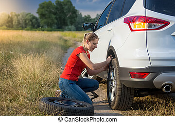 Young woman changing flat tire on the rural road