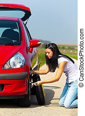 Young Woman Changing Tire - Young woman changing tire by the...