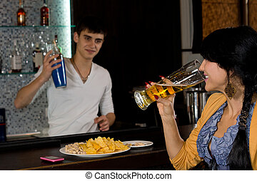 Young woman chatting to the barman