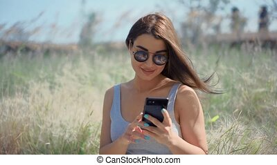 Young woman chatting with friends by smartphone in the sunny park.