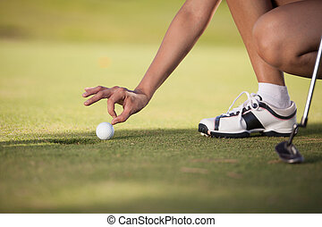 Young woman cheating at golf
