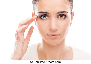 Young woman checking her face skin