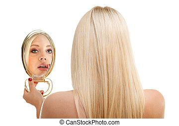 Young woman checking her hair in mirror