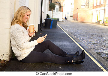 young woman checking her phone with a coffee