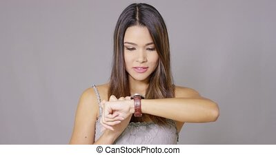 Young woman checking her watch for the time - Young woman...