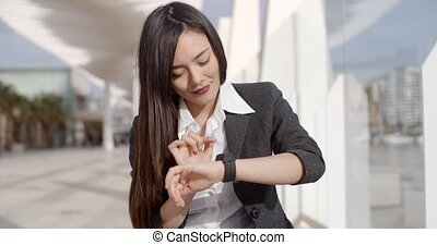 Young woman checking her wristwatch for the time