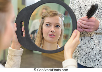 young woman checks her hair in the mirror