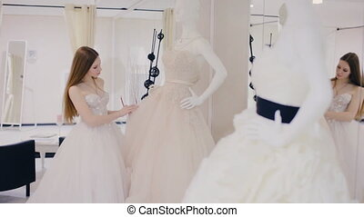 Young woman chooses a wedding dress in bridal shop