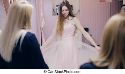 Young woman chooses a wedding dress in bridal shop - Pretty...
