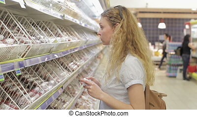 Young woman chooses baby goods in the supermarket