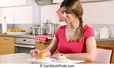 Young woman chooses between an apple and a cream cake - ...