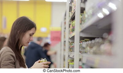 Young woman chooses canned food in the store - young woman...
