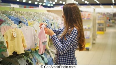 young woman chooses clothes for a child in the supermarket