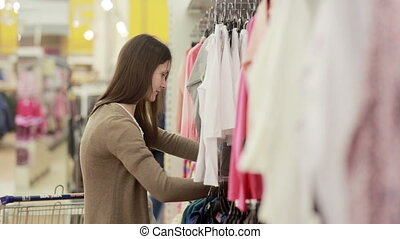 young woman chooses clothes for a child