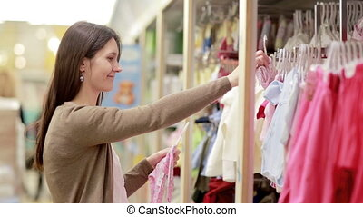 young woman chooses clothes for newborn baby - young smiling...