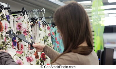 young woman chooses clothes in store