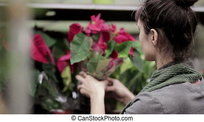 Young woman chooses flowers in the store