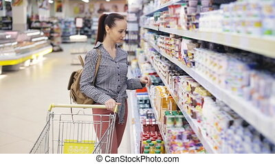 Young woman chooses food in the supermarket