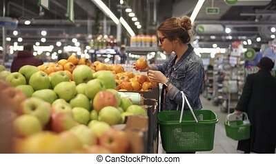 Young woman chooses fruit oranges in the store
