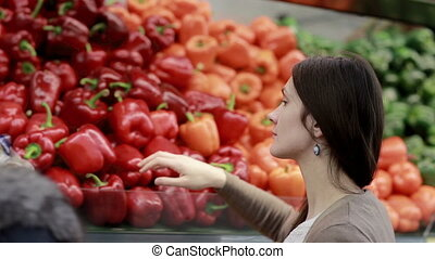 Young woman chooses paprika on store shelves.