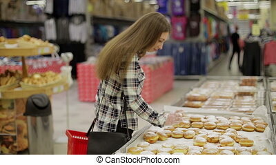 Young woman chooses products in the supermarket