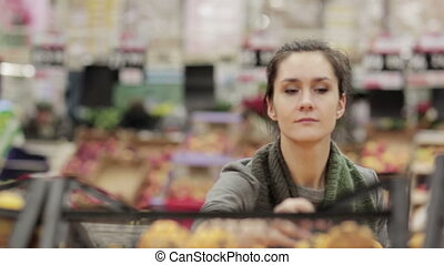 Young woman chooses ripe oranges on store shelves.