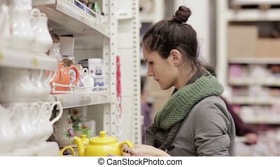 Young woman chooses shelves in the supermarket - young woman...
