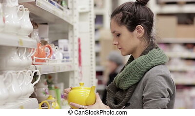 Young woman chooses shelves in the supermarket