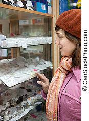 woman chooses  socket in  electrical store