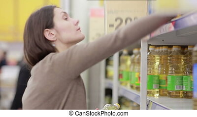 Young woman chooses sunflower oil in the store - young woman...