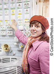 woman chooses  switch in  electrical store