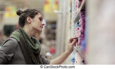 Young woman chooses towels in the supermarket
