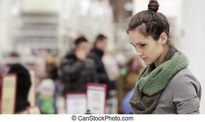 young woman looking at shelves in supermarket chooses winter hat