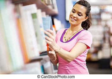 woman choosing a book in bookstore - young woman choosing a ...
