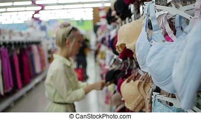 Young woman choosing a bra in the store