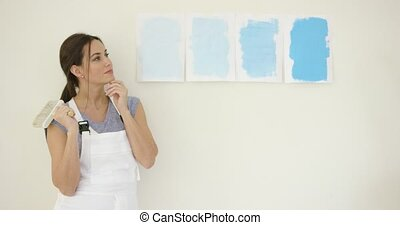 Young woman choosing a new paint for her home standing...