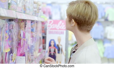 Young woman choosing beautiful doll in supermarket